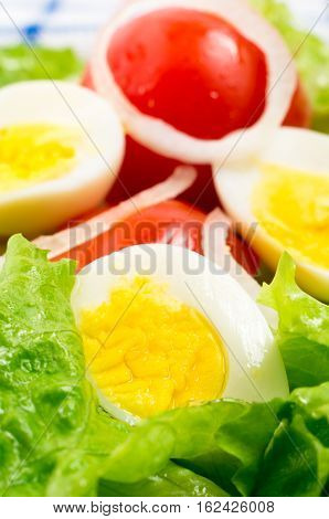 Boiled Eggs And Cherry Tomatoes In A Salad With Lettuce Leaves