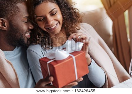 Lovely day with my soulmate. Cheerful smiling happy African American getting the box with the present and sitting in the cafe with her boyfriend while being covered with the blanket