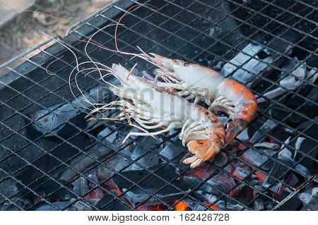 Fresh shrimp grilled on flaming grill. .
