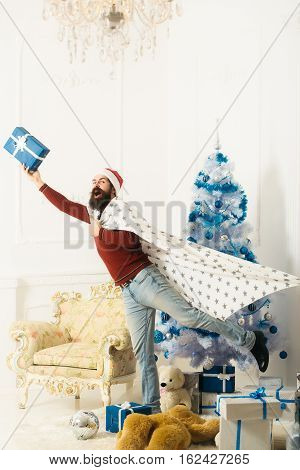 christmas bearded man in red sweater and santa claus hat at xmas blue decorated tree. happy guy at new year holidays celebration holds present box near bear toy ball arm chair on white brick wall