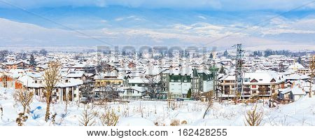 Houses with snow roofs and church tower panorama banner of bulgarian ski resort Bansko, Bulgaria
