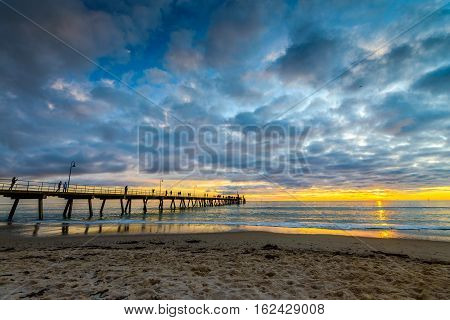 People walking along Glenelg Beach jetty at sunset South Australia