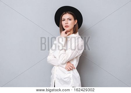Portrait of a young pensive woman in hat standing and posing isolated on a gray background