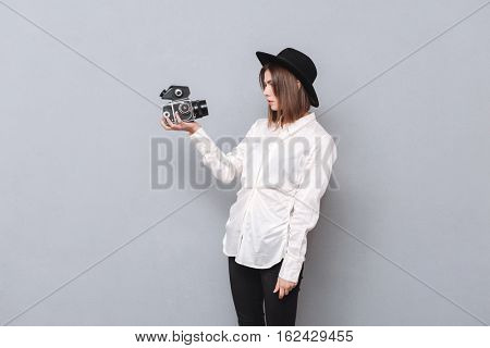 Portrait of a young woman in hat standing and making a video with camera isolated on the gray background