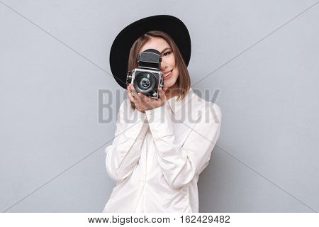 Portrait of a young smiling woman filming with retro camera isolated on the gray background