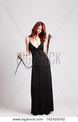 fashion model red-haired girl in long black evening dress studio shot