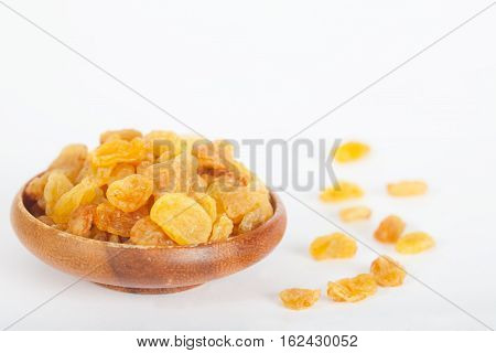 Yellow raisins or sultanas in a small wooden bowl on white background