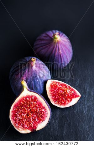 Fresh blue figs on black background. Beautiful violet figs with empty copy space close up