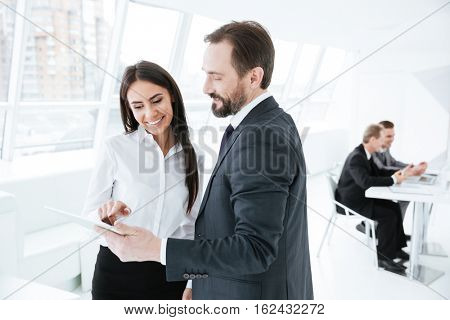 Business partners looking at tablet in office with colleagues on background