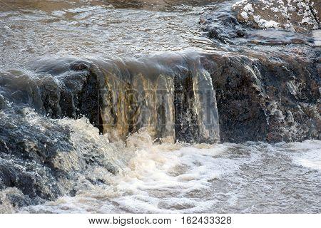 Small beautiful waterfall in rapids on winter.