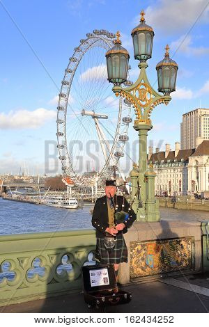LONDON, UK - DECEMBER 31, 2015: Scottish musician playing bagpipes at sunset on Westminster Bridge with London Eye in the background