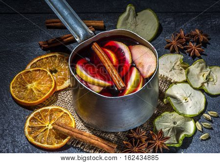 Small stewpot with mulled wine and cinnamon sticks, dry slice of oranges and apple, star anise on a dark table