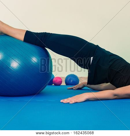 Woman exercising with fitness ball, toned image, square image
