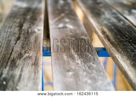 Old weathered timber planks on an outdoor deck or bench with a shallow dof view along the length of the wooden boards