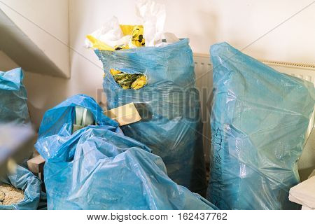 Blue plastic bags full of used building materials and waste