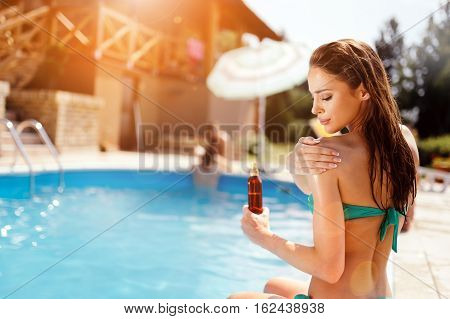 Woman applying sun uv protection lotion at summer