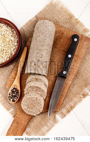 homemade irish white pudding with oatmeal and spices on a wooden board