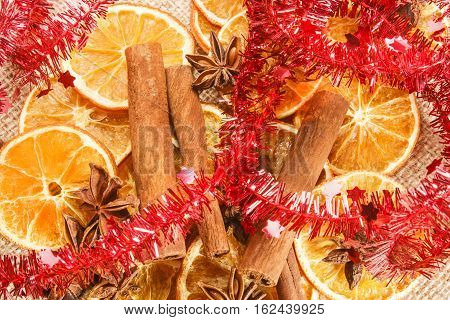 christmas decoration with orange slices cinnamon sticks anise stars and red tinsel garland