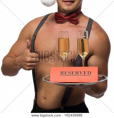Bartender with a naked torso showing thumbs up holding two glasses of champagne in reserve