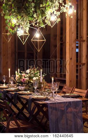 Decoration festive table before a banquet. Above the table garland with the lamps.