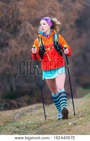 Young Blonde Girl Active Practice Nordic Walking In A Mountain Meadow