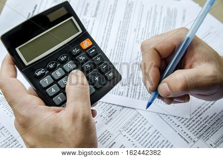 Cropped image of Businessman calculating and checking tax