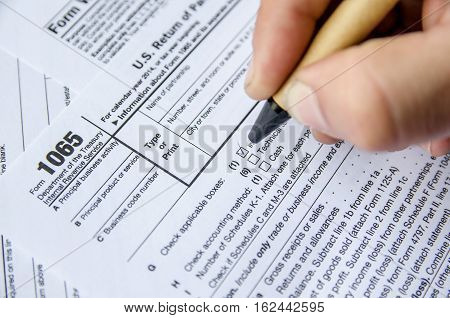 Person completing 1065 tax form. business concept