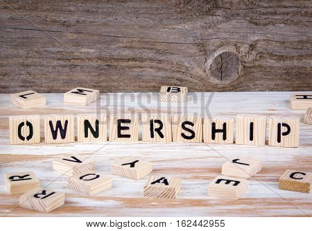 Ownership from wooden letters on wooden background