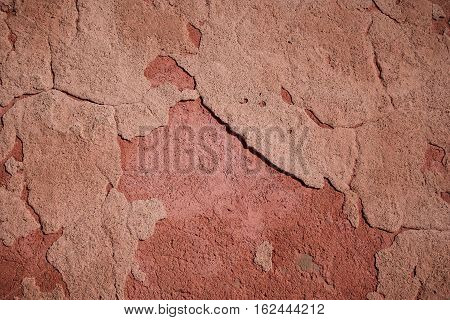Distressed patchy red cement render faded by the sun