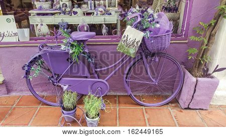 Lavender bicycle decorated with sprigs of lavender for advertising outside gift shop with colorful window display in Spain.