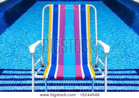 a deckchair in a swimming pool in the summer
