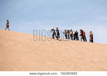 SAN PEDRO DE ATACAMA, CHILE-NOV.10,2016: Sand boarders await their turn to zoom through the red sand dunes of Death Valley in Chile's Atacama Desert.