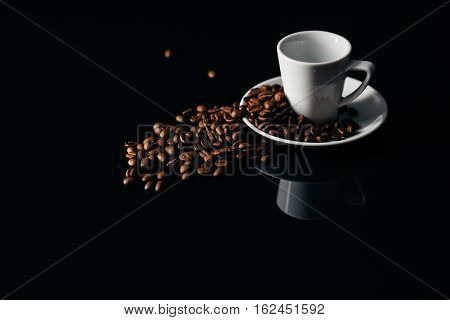 Overturned white mug with coffee beans on desk