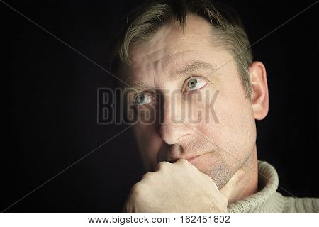 Dreamily looking man posing with a hand under his chin cropped studio portrait