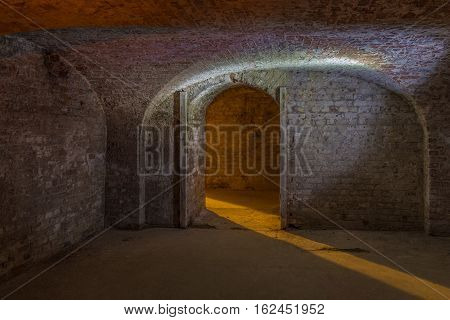 Cellar room made of brick with curved ceiling with an entrance showing a shaft of light beaming in.