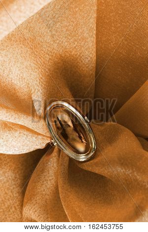 Amber golden ring on yellow draped cloth as a background