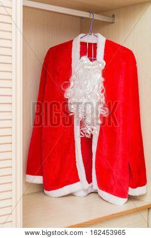 Santa Claus Coat and Beard hanging in a wardrobe
