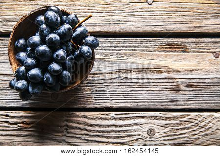 Top view of grapes in wicker basket on wooden table. fruits