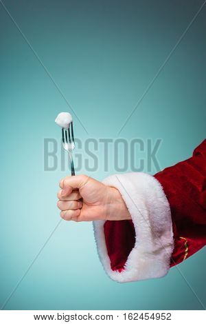 The Santa hand holding a fork with snow and ready for Christmas time on blue studio background