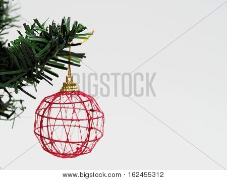 Red Christmas ball hanged on green christmas pine tree branch isolated on white background