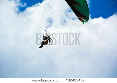 Person flying with para motor  under the cloudy and blue sky