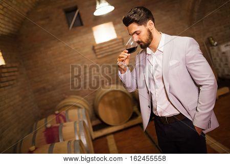 Winemaker inspecting wine in modern winery basement