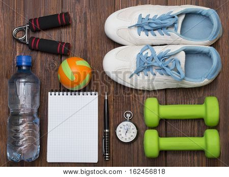 Workout and fitness dieting copy space diary. Healthy lifestyle concept. Apple, dumbbell, water, expander hand, stopwatch and measuring tape on rustic wooden table.