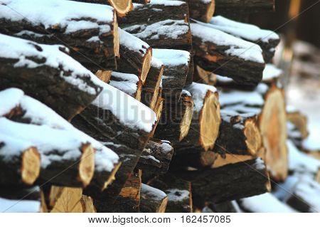 Snowbound woodpile under rural shed. Winter background.