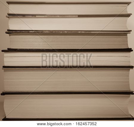 Abstract - stack of old book side view - sepia background