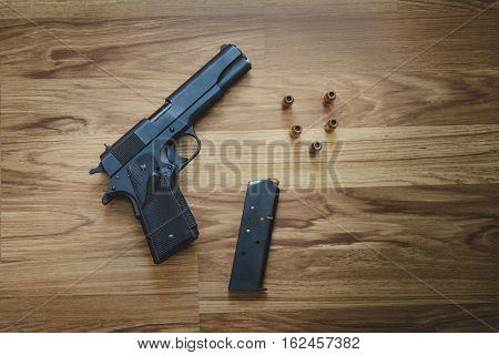 Top View Of Pistol Semi-automatic .45 Caliber With Magazine And Bullet On The Wooden Table
