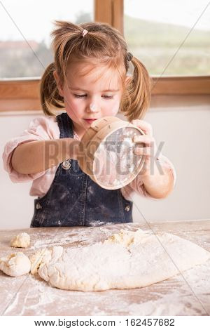 Little girl baking, playing with flour and sieve
