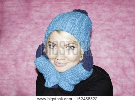 Portrait of a girl in blue knitted cap and mittens up on a pink background. Snow maiden