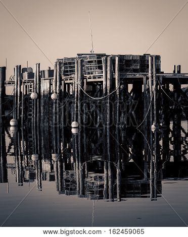 Old wooden wharf reflects in the water in Nova Scotia