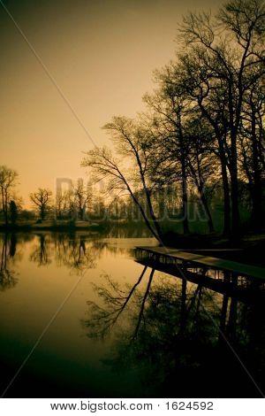 Sun setting on a calm lake with